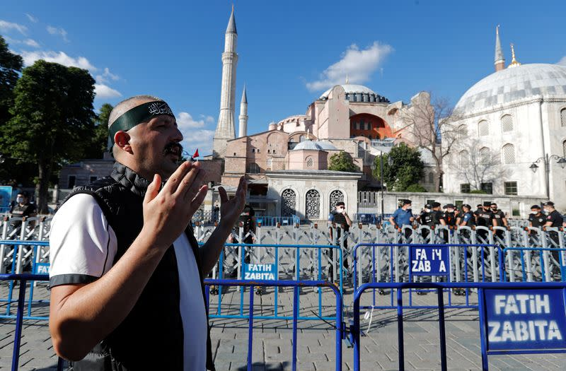 A Muslim man prays in front of the Hagia Sophia or Ayasofya, after a court decision that paves the way for it to be converted from a museum back into a mosque, in Istanbul