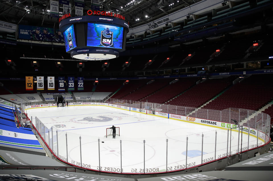 VANCOUVER, BC - MARCH 31: A rink attendant pushes a game net off the ice after the NHL game between the Calgary Flames and the Vancouver Canucks was postponed due to a positive COVID test result of a player at Rogers Arena on March 31, 2021 in Vancouver, British Columbia, Canada.  (Photo by Jeff Vinnick/NHLI via Getty Images)