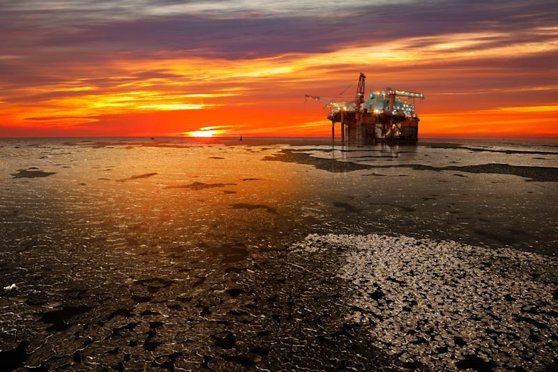 An offshore oil rig platform with the sun rising on a frozen sea