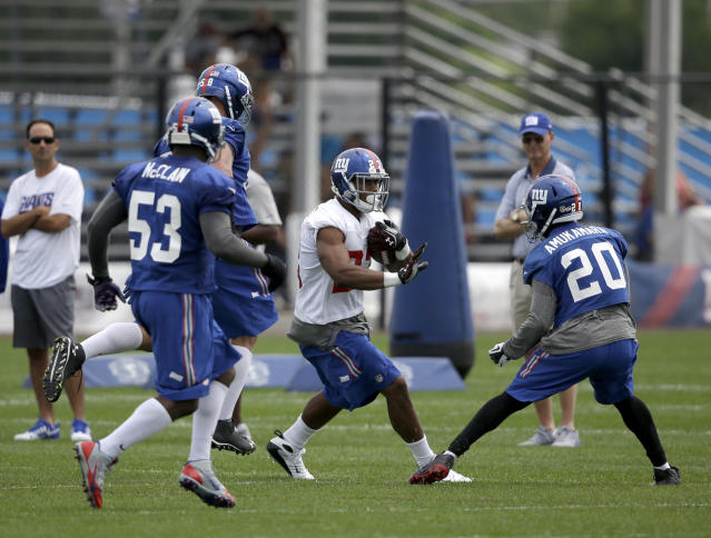 New York Giants running back Rashad Jennings, second from right, runs the ball during NFL football camp in East Rutherford, N.J., Thursday, July 24, 2014. (AP Photo/Seth Wenig)