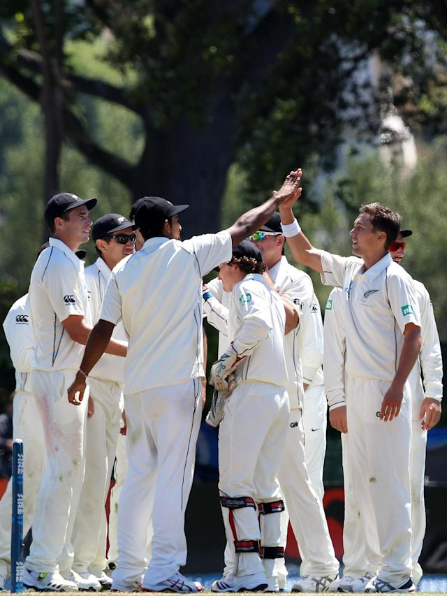 DUNEDIN, NEW ZEALAND - DECEMBER 05: Trent Boult of New Zealand is congratulated by his team-mates after taking the wicket of Kieron Powell during day three of the first test match between New Zealand and the West Indies at University Oval on December 5, 2013 in Dunedin, New Zealand. (Photo by Rob Jefferies/Getty Images)