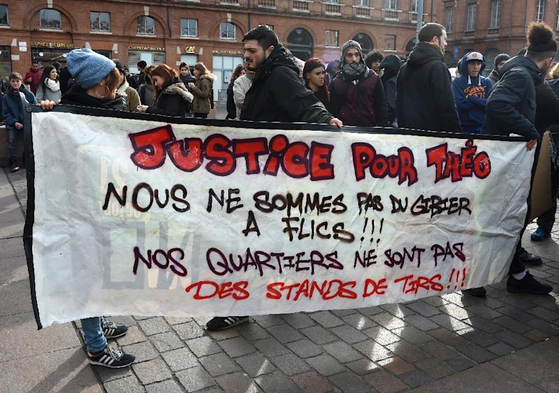 "People hold a banner reading ""Justice for Theo, we are not prey for the police, our neighbourhoods are not shooting ranges"" during a gathering at the Capitole Square in Toulouse on February 11, 2017, in support of Theo, a 22-year-old youth worker (AFP Photo/Eric CABANIS)"