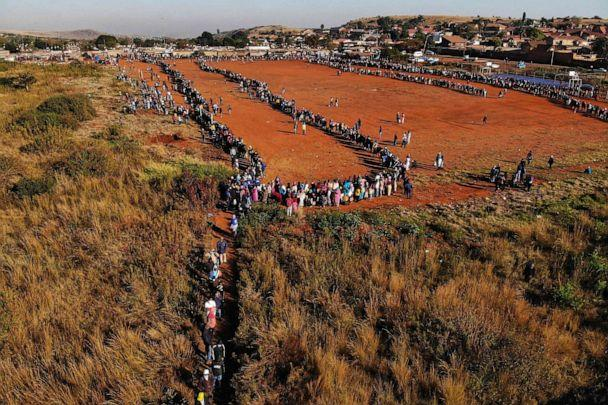 PHOTO: This aerial view shows people queueing during a distribution of hampers, masks, soap and sanitizer organized by different charities at the Iterileng informal settlement near Laudium suburb in Pretoria, South Africa, on May 20, 2020. (Marco Longari/AFP via Getty Images)