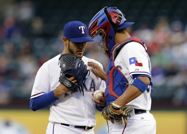 Texas Rangers' Martin Perez talks to catcher Robinson Chirinos, right, on the mound after giving up a two-run double to Oakland Athletics' Derek Norris in the first inning of a baseball game, Tuesday, April 29, 2014, in Arlington, Texas. (AP Photo/Tony Gutierrez)