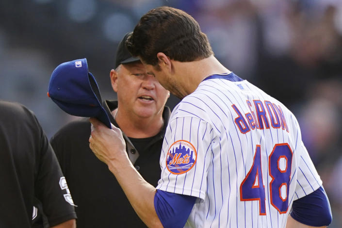 Third base umpire Ron Kulpa, left, looks inside the cap of New York Mets starting pitcher Jacob deGrom (48) after deGrom pitched in the top of the fifth inning of a baseball game against the Atlanta Braves, Monday, June 21, 2021, in New York. (AP Photo/Kathy Willens)