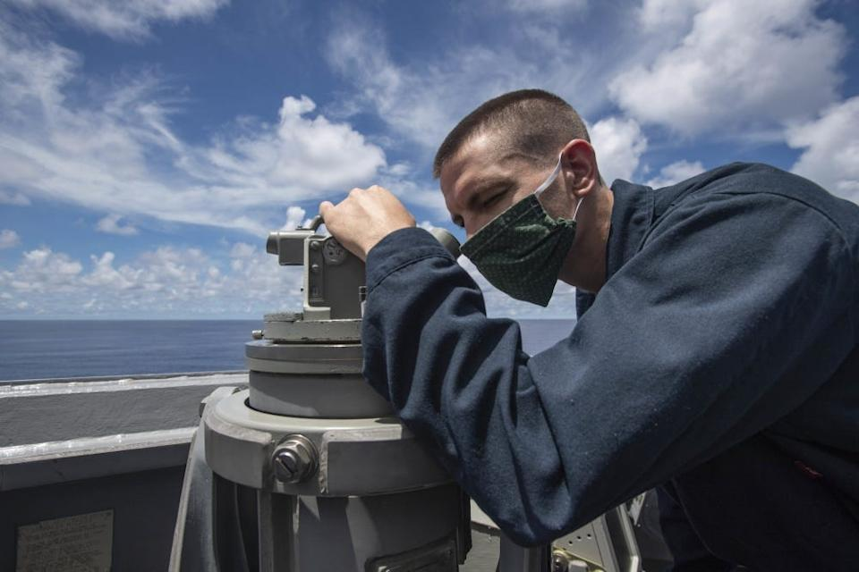 Logistics Specialist 2nd Class Paul Vance, from Lilburn, Ga., assigned to the Arleigh Burke-class guided-missile destroyer USS Ralph Johnson (DDG 114), scans the horizon using a telescopic alidade, July 14, near the Spratly Islands in the South China Sea