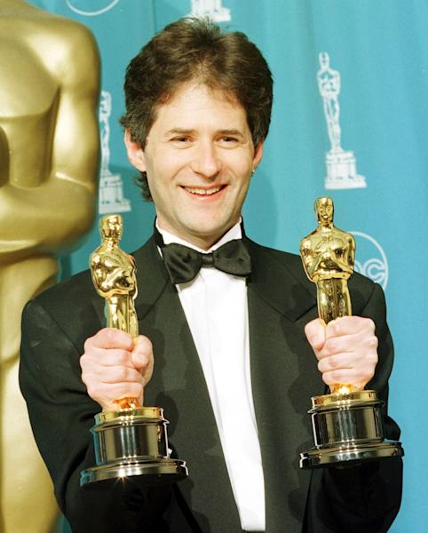 "Composer James Horner holds his two Oscars for Best Original Song for ""My Heart Will Go On"" and Best Dramatic Score for Titanic at the 70th Annual Academy Awards in Los Angeles in 1998 (AFP Photo/Hal Garb)"