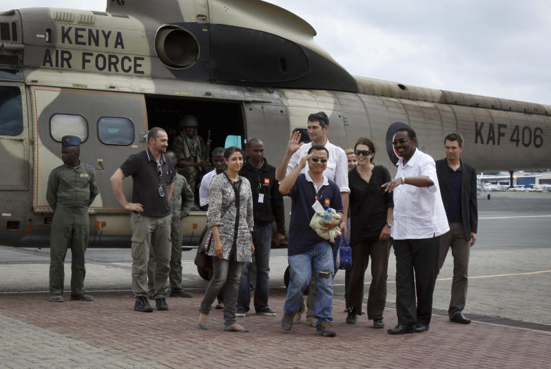Released aid workers Qurat-Ul-Ain Sadazai, 38, a Canadian citizen of Pakistani origin, center-left, Glenn Costes of the Philippines, 40, center-right, Steven Dennis of Canada, 37, above-center-right, and Astrid Sehl of Norway, 33, 3rd-right, arrive back by Kenyan military helicopter at Wilson airport in Nairobi, Kenya, Monday, July 2, 2012. A pro-government Somali militia group said Monday that it rescued the four aid workers kidnapped by gunmen from a refugee camp in Kenya last week. (AP Photo/Farah Abdi Warsameh)
