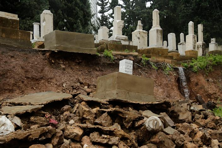 CORRECTS TO CAPITAL'S ONLY JEWISH CEMETERY, NOT COUNTRY'S - Graves from a Jewish cemetery lie on a sidewalk after it collapsed following heavy rains in the Sodeco area of Beirut, Lebanon, Thursday, Dec. 26, 2019. A heavy storm hit Lebanon with heavy rain and strong winds causing an old wall to collapse in the capital's only Jewish cemetery, causing damage to several tombstones. Lebanon once had a thriving Jewish community, but the various Arab-Israeli wars and Lebanon's own 1975-90 civil war caused waves of emigration and almost none are left in the country today. (AP Photo/Hassan Ammar)