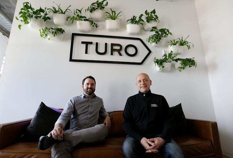 In this April 29, 2019, photo, Steve Webb, VP of Communications, left, and Andre Haddad, CEO, right, pose in the entryway of Turo in San Francisco. Car-sharing apps that let people rent out their vehicles to strangers are growing in popularity in the U.S. But the people who rent cars through apps like Turo and GetAround don't pay the taxes and surcharges that local governments and airports tack onto traditional rental cars. (AP Photo/Eric Risberg)