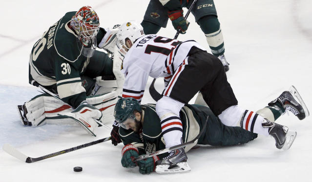 Chicago Blackhawks center Jonathan Toews (19) and Minnesota Wild defenseman Marco Scandella, bottom, battle for the puck in front of Wild goalie Ilya Bryzgalov (30), of Russia, during the third period of Game 3 of an NHL hockey second-round playoff series in St. Paul, Minn., Tuesday, May 6, 2014. The Wild won 4-0. (AP Photo/Ann Heisenfelt)