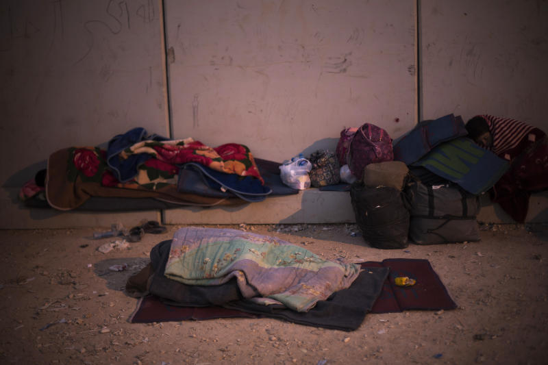In this Thursday, Oct. 24, 2013, photo, Syrian refugees sleep covered with blankets at the new arrivals point at the Zaatari refugee camp near the Syrian border in Jordan. With Syria's civil war in its third year, more than 2 million Syrians have fled their country. About 100,000 live in this camp. (AP Photo/Manu Brabo)