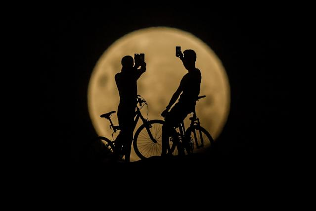 <p>People with bicycles take photos of the Super moon on Jan. 31, 2018 in Lancelin, Australia. (Photo : Paul Kane/Getty Images) </p>