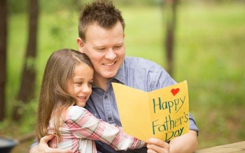 father excitedly receives a homemade card from his daughter - Credit: E+