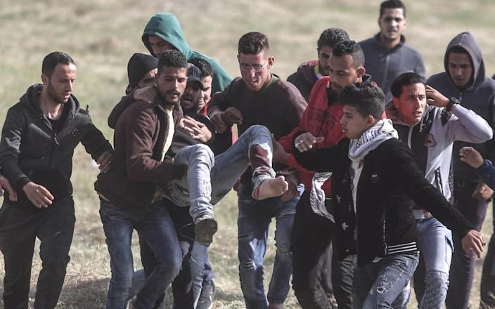 A wounded Palestinian demonstrator is being moved away after clashes with Israeli troops - Anadolu
