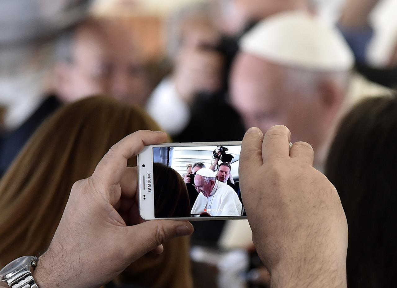 <p>A person takes a photo of Pope Francis with a mobile phone during his flight to Portugal, prior to visiting Fatima shrine on May 12, 2017. (Photo: Tiziana Fabi/AFP/Getty Images) </p>