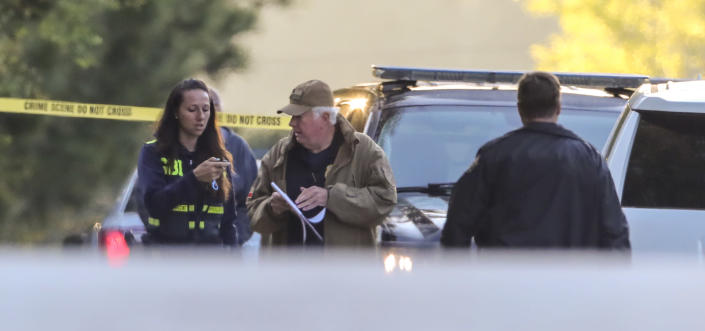 A Georgia Bureau of Investigation officer confers with a Carroll County Sheriff deputy while investigating the scene after three metro Atlanta officers were injured Monday, April 12, 2021, after a police chase entered Carroll County, Ga., and a passenger fired multiple rounds with a rifle, officials said. Georgia authorities said one suspect was killed and the other arrested following the chase. (John Spink/Atlanta Journal-Constitution via AP)