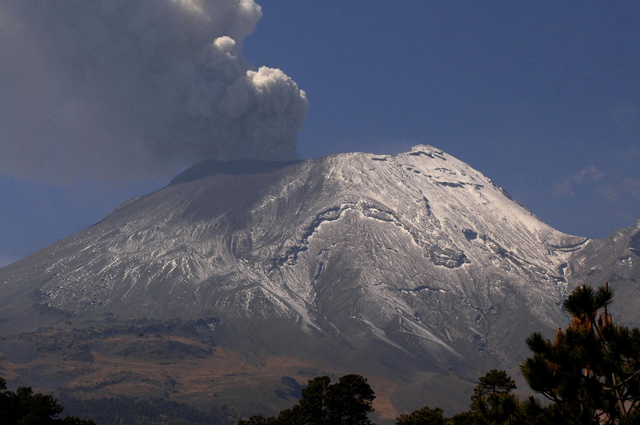 A plume of ash and smoke rises from the Popocatepetl volcano seen from the outskirts of the town of Santiago Xalizintla, Mexico, Friday, April 20, 2012. Authorities prepared evacuation routes, ambulances and shelters in the event of a bigger explosion after the volcano that looms over Mexico City emitted a low-pitched roar early Friday morning and spewed ash and steam. (AP Photo/Gonzalo Perez)