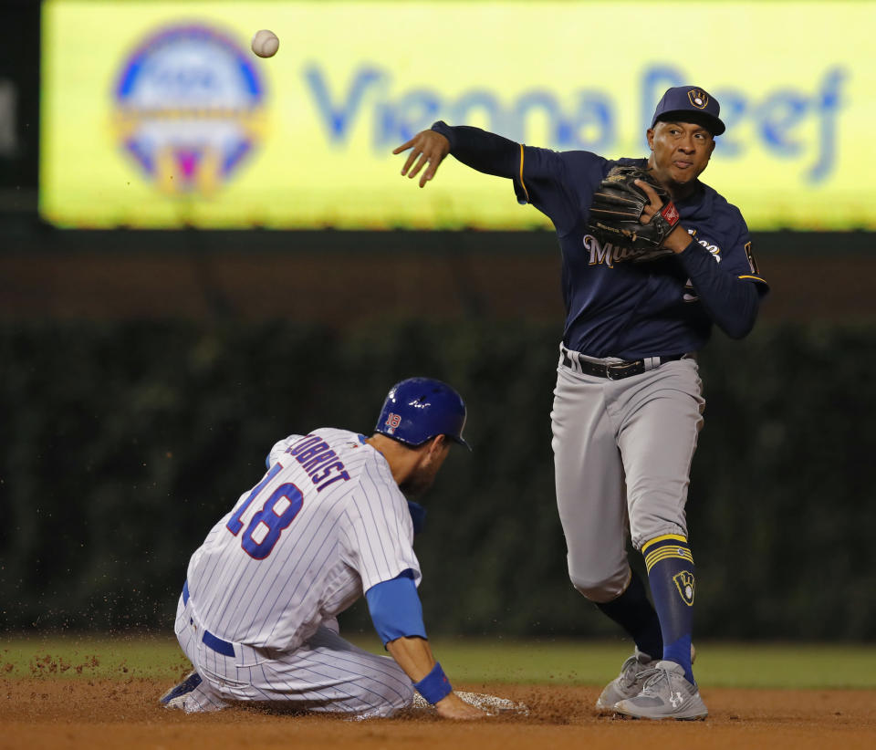 Milwaukee Brewers' Jonathan Schoop, right, makes a throw to first base as Chicago Cubs' Ben Zobrist is out at second base during the fourth inning of a baseball game Monday, Sept. 10, 2018, in Chicago. (AP Photo/Jim Young)