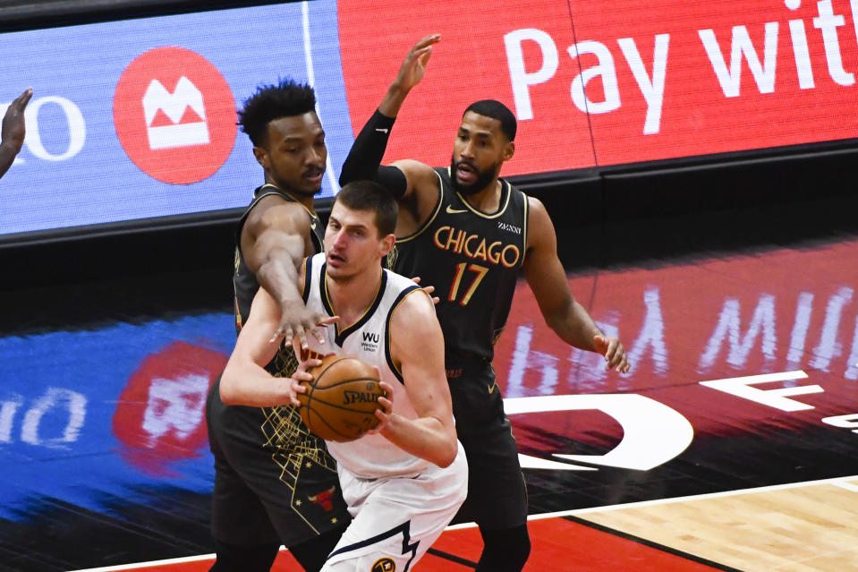 Denver Nuggets center Nikola Jokic, center, moves the ball away from Chicago Bulls center Wendell Carter Jr., left, and Garrett Temple (17) during the first half of an NBA basketball game Monday, March 1, 2021, in Chicago. (AP Photo/Matt Marton)