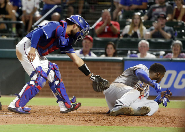 Texas Rangers catcher Isiah Kiner-Falefa holds the ball after tagging out Los Angeles Dodgers' Yasiel Puig, who tried to steal home during the seventh inning of a baseball game Wednesday, Aug. 29, 2018, in Arlington, Texas. (AP Photo/Michael Ainsworth)