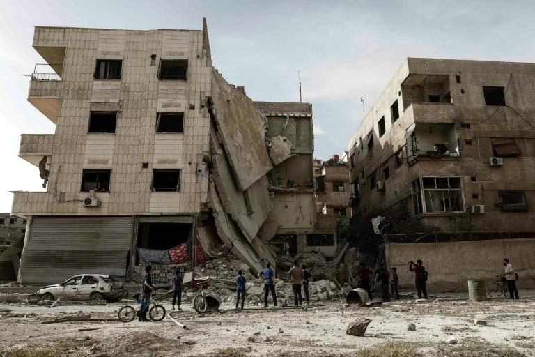 People inspect a hospital, damaged following an air strike a rebel-controlled town in the eastern Ghouta region on the outskirts of the capital Damascus on May 1, 2017