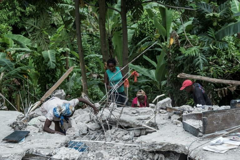 People look search through rubble looking for blankets at their crumbled home near Camp-Perrin, Haiti on August 16, 2021