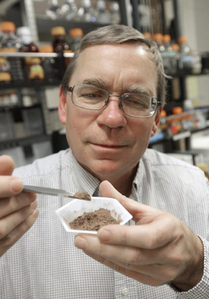 In this photo taken Friday, Dec. 22, 2012, Carl Keen, who serves as chairman of the developmental nutrition program at the University of California, Davis, poses with cocoa powder in one of the schools research laboratories at the Davis, Calif. Keen, whose position is funded by the candy giant Mars Inc., said his laboratory's findings have pushed science forward through establishing that nutrients in cocoa powder can lower heart disease risk.(AP Photo/Rich Pedroncelli)