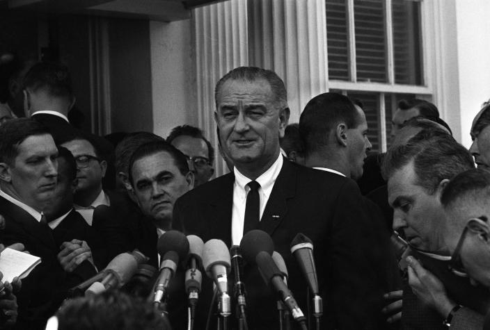 With Alabama Gov. George Wallace looking over his shoulder, President Lyndon Johnson, center, speaks to reporters outside the White House on March 13, 1965, in Washington, D.C. (Photo: AP)