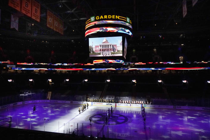 Boston Bruins and Philadelphia Flyers players stand for the national anthem before the Bruins' home-opener NHL hockey game, Thursday, Jan. 21, 2021, in Boston. (AP Photo/Elise Amendola)