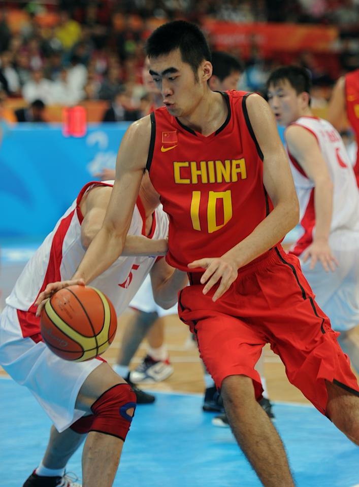 Zhaoxu Zhang (R) of China competes against O Jin Hyok of North Korea at the basketball men's preliminary round group E game 11 during the 16th Asian Games in Guangzhou on November 17, 2010. China won 98-62.  AFP PHOTO / Sam YEH (Photo credit should read SAM YEH/AFP/Getty Images)