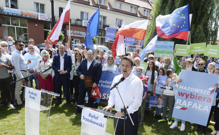 In this Thursday, July 9, 2020 photo Rafal Trzaskowski, front, contender in Poland's tight presidential election runoff on Sunday, July 12, 2020, speaks to supporters during a rally in Raciaz, Poland. Trzaskowski is running against incumbent conservative president, Andrzej Duda, who has backing from the ruling party. Opinion polls suggest the election may be decided by a small number of votes. (AP Photo/Czarek Sokolowski)
