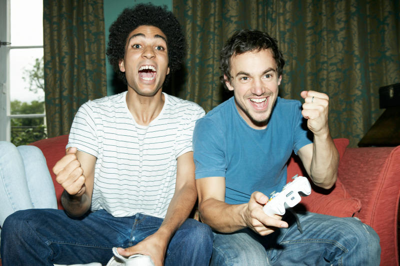 Two men celebrating while they play a video game,