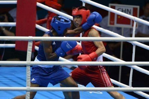 Ren Cancan of China (in red) defends against Nicola Adams of Great Britain (in blue) during the women's boxing Flyweight final of the 2012 London Olympic Games at the ExCel Arena August 9, 2012 in London. Nicola Adams defeated Cancan Ren to win gold