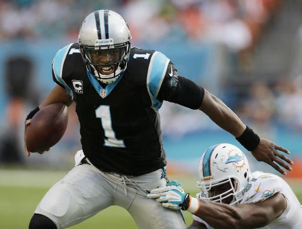 Carolina Panthers quarterback Cam Newton (1) runs from a tackle by Miami Dolphins defensive end Cameron Wake (91) during the second half of an NFL football game on Sunday, Nov. 24, 2013, in Miami Gardens, Fla. The Panthers defeated the Dolphins 20-16. (AP Photo/Alan Diaz)