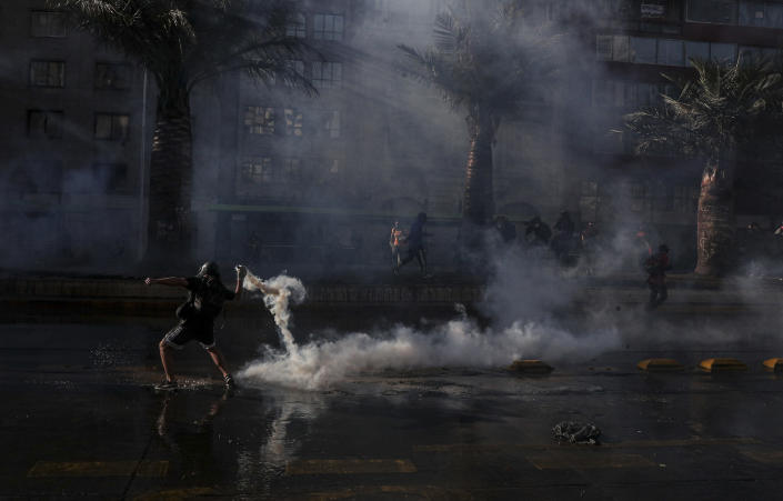 A demonstrator returns a tear gas canister fired by police during a protest against police in reaction to a video that appears to show an officer pushing a youth off a bridge the previous day at a protest, in Santiago, Chile, Saturday, Oct. 3, 2020. (AP Photo/Esteban Felix)