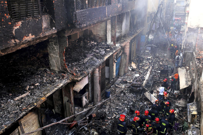 In this, Thursday, Feb. 21, 2019 file photo, locals and firefighters gather around buildings that caught fire late Wednesday, Feb. 20 in Dhaka, Bangladesh. After more than 1,100 people died when a garment factory complex collapsed in Dhaka, Bangladesh authorities imposed more stringent safety rules. But corruption and lax enforcement have resulted in many more deaths linked to safety lapses since the 2013 Rana Plaza disaster, including a fire Thursday in an illegally-constructed high-rise office building that killed at least 25 people and left dozens more injured. (AP Photo/Rehman Asad, File)