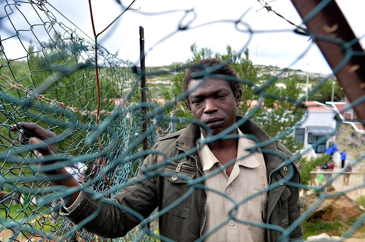 A migrant stands behind a fence of the 'Temporary Permanence Centre' (CPT), a refugee camp on February 17, 2015 in Lampedusa. The Italian coastguard launched a massive operation Sunday to rescue more than 2,000 migrants in difficulty between the Italian island of Lampedusa and the Libyan coast, local media said. The emergency rescue came on the same day Italy said it was evacuating staff from its embassy in Libya and suspending operations there, highlighting the worsening security situation in the violence-plagued country. AFP PHOTO / ALBERTO PIZZOLI (Photo credit should read ALBERTO PIZZOLI/AFP/Getty Images)