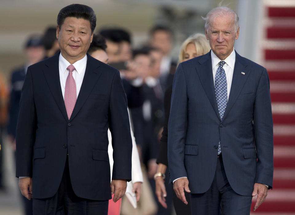 FILE - In this Sept. 24, 2015 file photo, Chinese President Xi Jinping and Vice President Joe Biden walk down the red carpet on the tarmac during an arrival ceremony in Andrews Air Force Base, Md. Chinese leaders hope Washington will tone down conflicts over trade, technology and security if Joe Biden wins the Nov. 3 presidential election. But any shift is likely to be in style, not substance, as frustration with Beijing increases across the American political spectrum. (AP Photo/Carolyn Kaster, File)