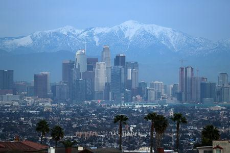Snow capped mountains are seen behind the downtown Los Angeles skyline