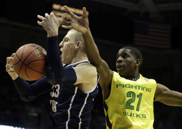 BYU forward Nate Austin (33) battle for a rebound against Oregon guard Damyean Dotson (21) during the first half of a second-round game in the NCAA college basketball tournament Thursday, March 20, 2014, in Milwaukee. (AP Photo/Morry Gash)