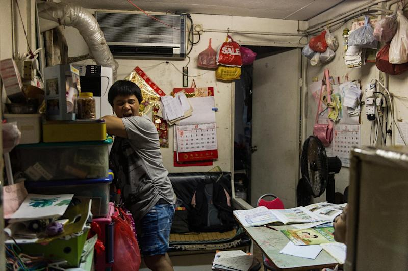 Su Xingyun (L), and her child (bottom R) in their two-room rooftop hut which is under a government removal order in the Sham Shui Po on October 10, 2013 (AFP Photo/Anthony Wallace)