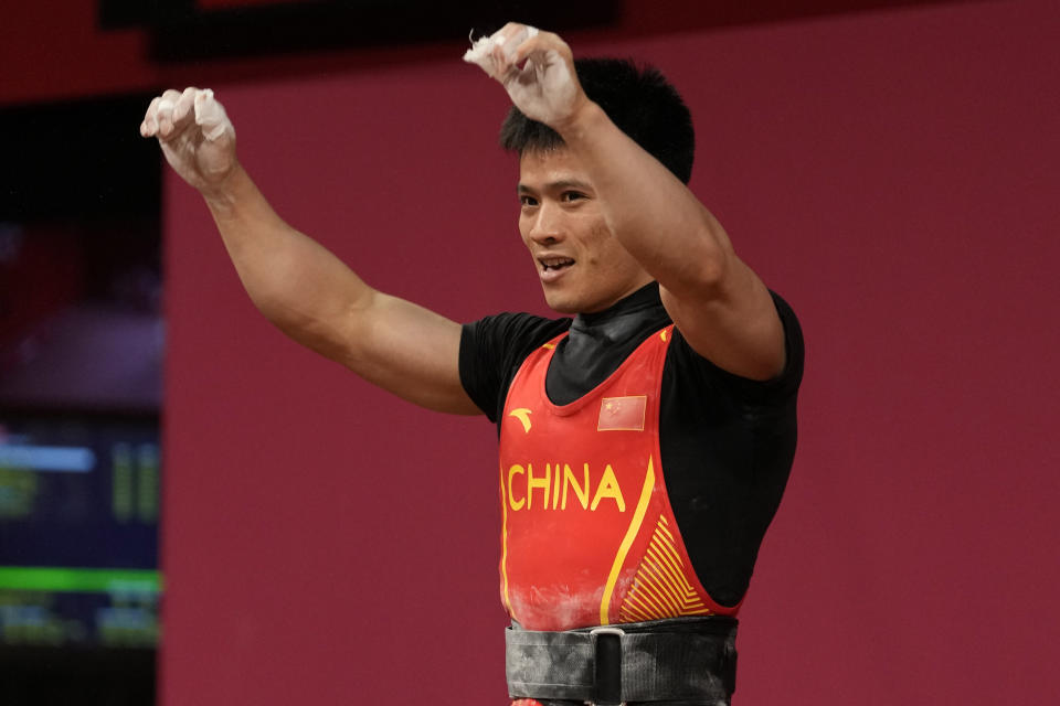 Li Fabin of China celebrates after a lift as he competes in the men's 61kg weightlifting event, at the 2020 Summer Olympics, Sunday, July 25, 2021, in Tokyo, Japan. (AP Photo/Luca Bruno)