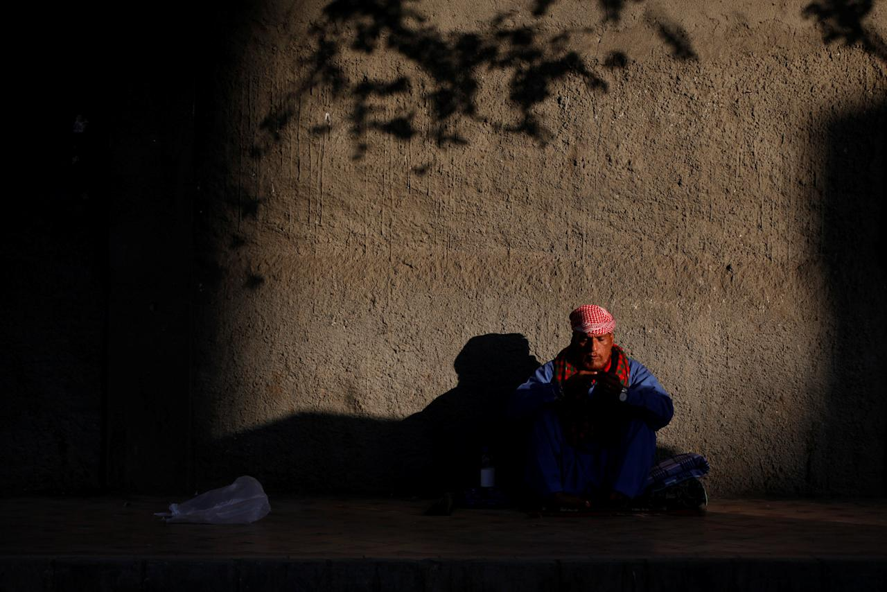 A man sits in the sunlight to warms himself along a side walk in the early morning in Karachi, Pakistan November 23, 2017. REUTERS/Akhtar Soomro
