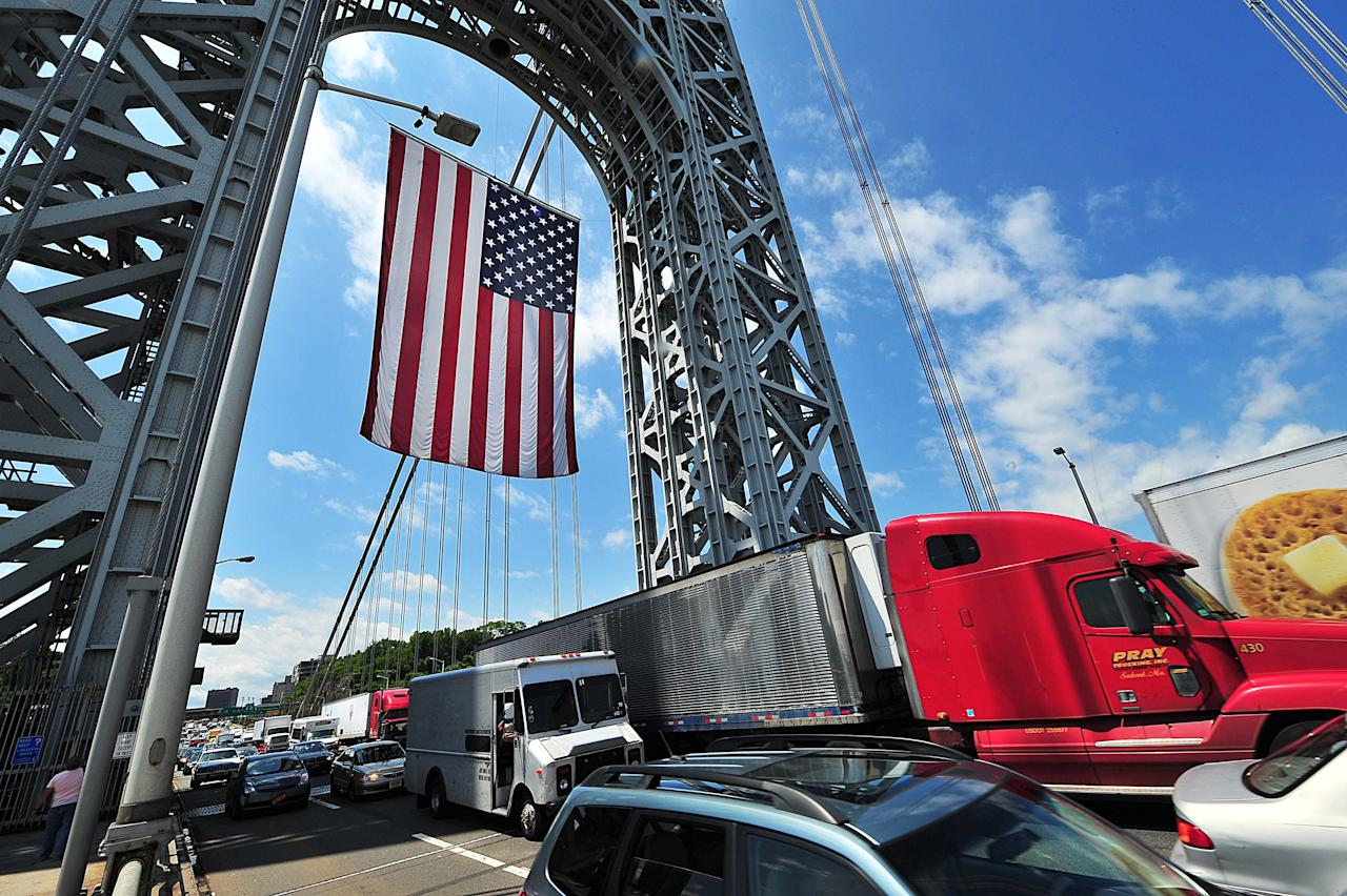 In this photo provided by the Port Authority of New York and New Jersey, traffic passes under a large American flag that hangs from the superstructure of the George Washington Bridge in New York, Friday, June 14, 2013, in observance of Flag Day. According to the Port Authority, the flag is one of the world's largest free-flying flags. (AP Photo/Port Authority of New York and New Jersey)
