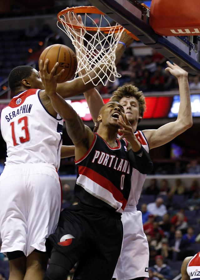 Portland Trail Blazers guard Damian Lillard (0) shoots as he is defended by Washington Wizards center Kevin Seraphin (13), of France, and forward Jan Vesely (24) in the first half of an NBA basketball game, Monday, Feb. 3, 2014, in Washington. (AP Photo/Alex Brandon)
