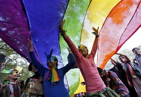 Participants dance under a a rainbow flag as they attend the sixth Delhi Queer Pride parade