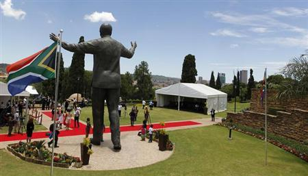 People stand near the 9-metre (30-feet) bronze statue of the late former South African President Nelson Mandela as it is unveiled as part of the Day of Reconciliation Celebrations at the Union Buildings in Pretoria December 16, 2013. REUTERS/Thomas Mukoya
