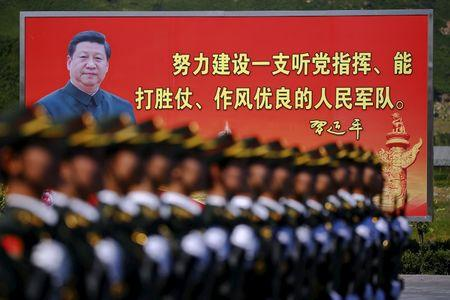 A picture of Chinese President Xi is seen on a billboard behind soldiers of China's People's Liberation Army marching during a training session at a military base in Beijing