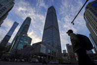 A man wearing a face mask and motorists pass through the skyscrapers at the Central Business District in Beijing, Tuesday, Nov. 24, 2020. China has reported new coronavirus cases in the cities of Shanghai and Tianjin as it seeks to prevent small outbreaks from becoming larger ones. (AP Photo/Andy Wong)